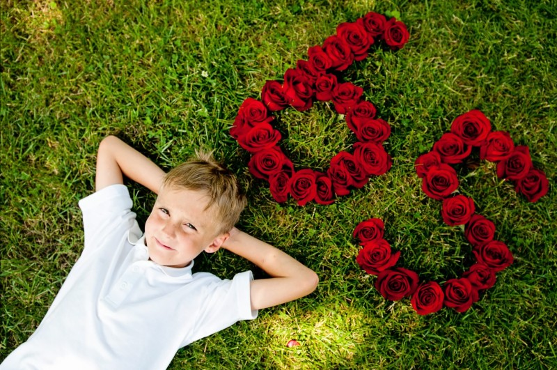 Brayden Walsh lying next to 65 roses, in order to promote his cause.  Photo Credit / Teresa Walsh