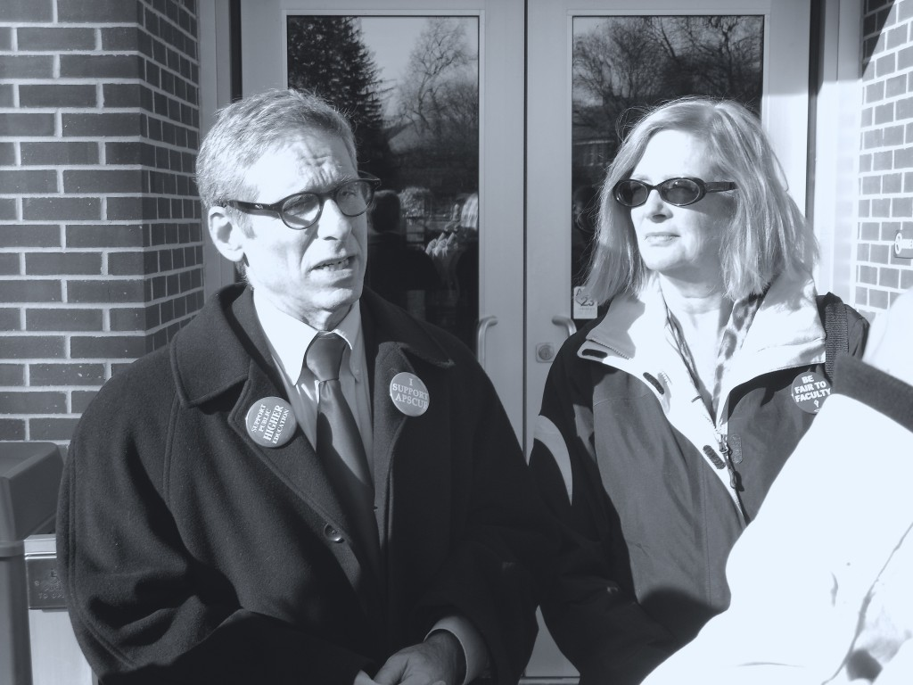 Dr. Alan Benn and Dr. Nancy Van Arsdale talk to students and faculty at a faculty march. Photo Credit / Jamie Reese