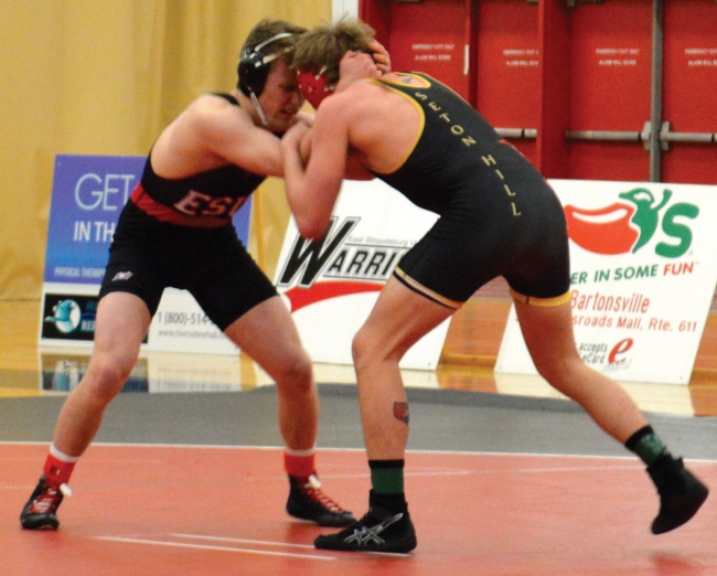 Two wrestlers from ESU and Seton Hill tangle on the mats. Photo Credit / Crystal Smith