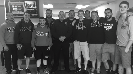 The members of Kappa Delta Rho with a member of the campus police. Photo Courtesy / Paul Novak