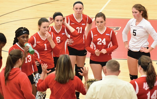 Junior libero #5 Rosa Veliky (in white) and the team listen to Coach Allison Keeley during a timeout. Photo Credit / Ronald Hanaki
