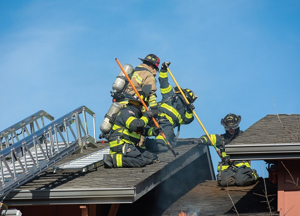 Firefighters on the roof of University Ridge putting the fire out. Photo Courtesy / Adam Walker