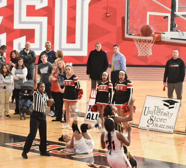 ESU's #25 Allison Howard (on the ground) scores and gets fouled for an old fashioned three-point play. Photo Credit / Ronald Hanaki