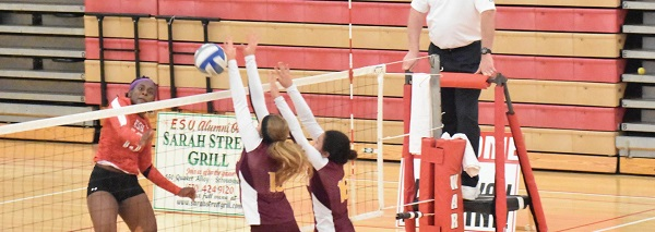Senior outside hitter #13 Desiree Claxton (left in red) goes for the kill. Photo Credit / Ronald Hanaki