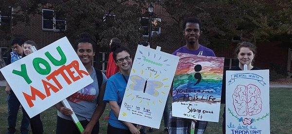Photo Credit / Ashley Levin From left, Sophia Cabrera, Alyssa Mesi, David James, and Zoe Maas hold up signs advocating the importance of mental health.